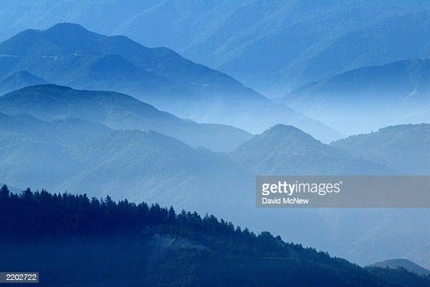 Pine forests can be seen among hazy ridges as increasing humidity and heat set the stage for lightning storms which could ignite flammable...