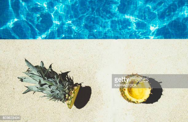 pineapple cut in half with a pool in the sun - poolside stock pictures, royalty-free photos & images