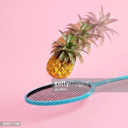 Pineapple flying toward badminton racket