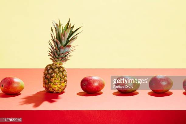 a pineapple in a row of mangos - tropical fruit stock pictures, royalty-free photos & images