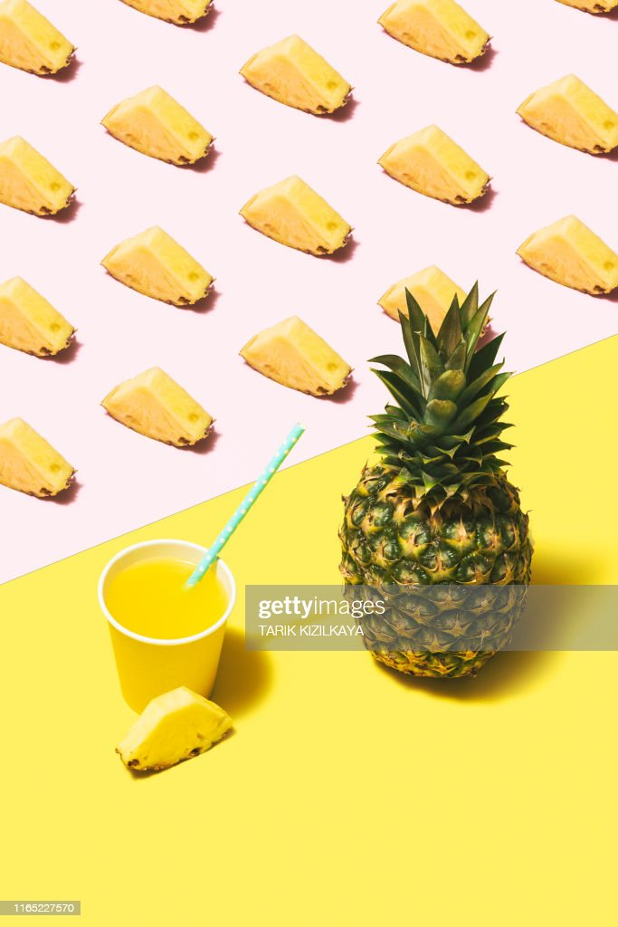 Pineapple juice flat lay on pink and yellow background : Stock Photo