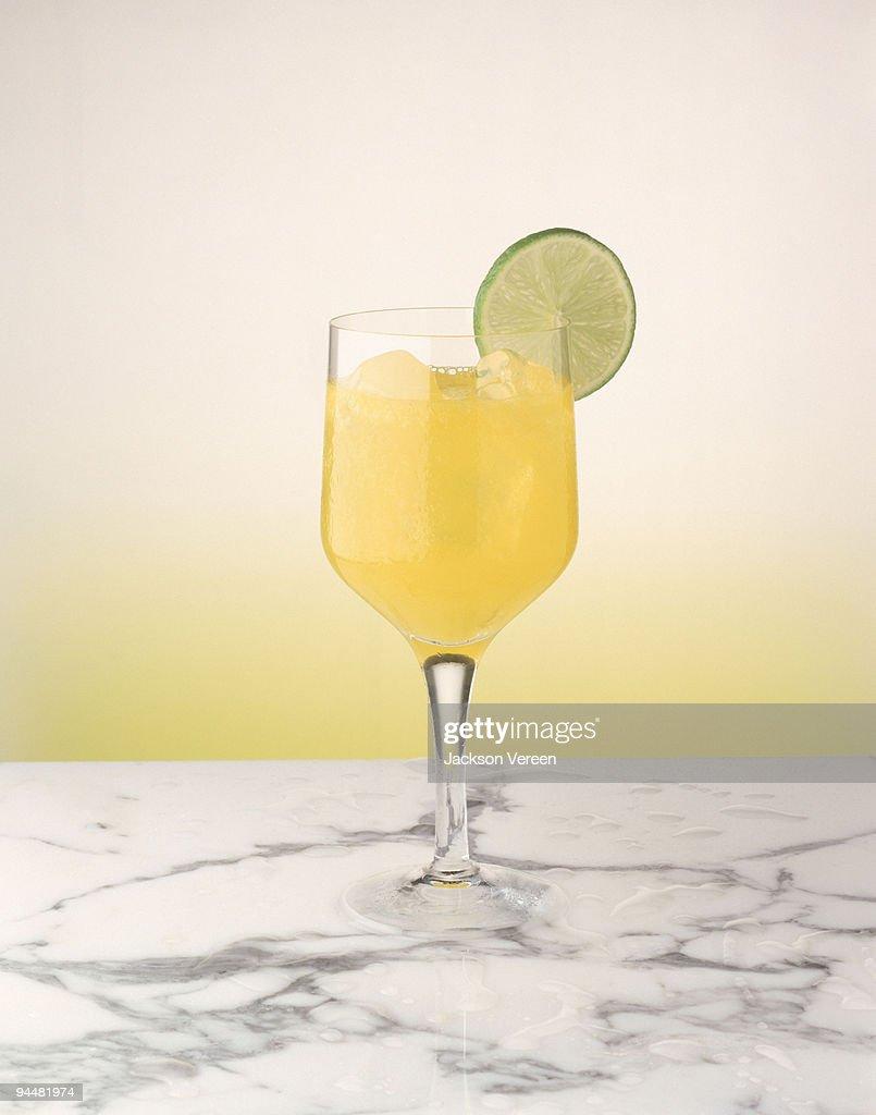 Pineapple juice with lime garnish : Stock Photo