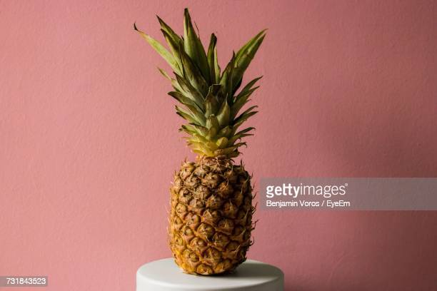 Pineapple On Table Against Pink Wall