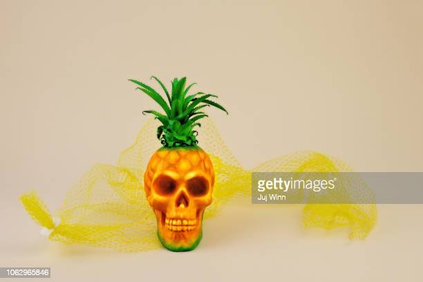 Pineapple skull on neutral background with yellow net