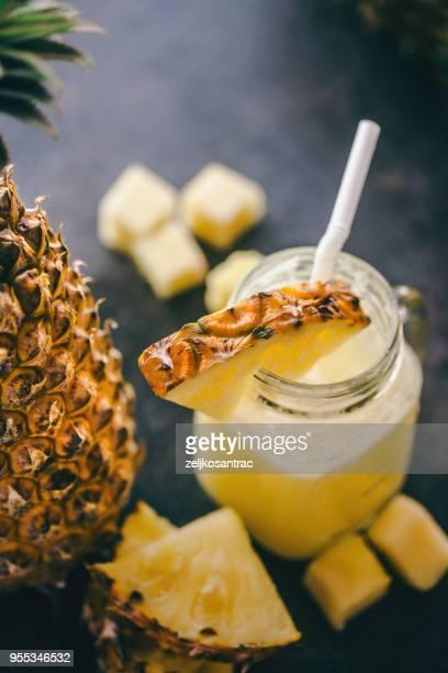 Ananas-smoothie mit frischer Ananas auf Holztisch