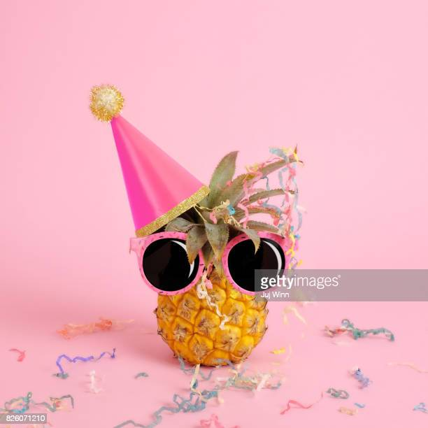 Pineapple wearing a party hat and sunglasses