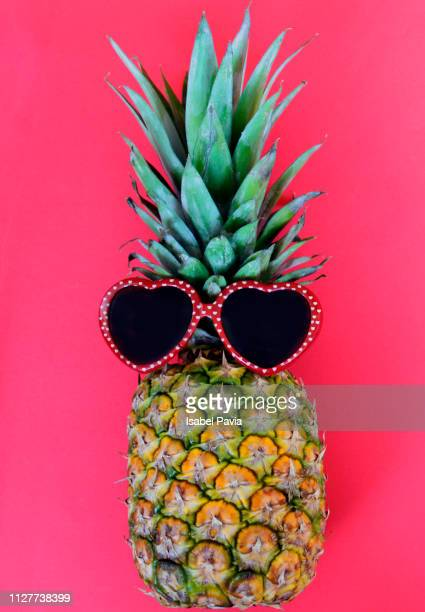 Pineapple with red heart shape sunglasses on red background