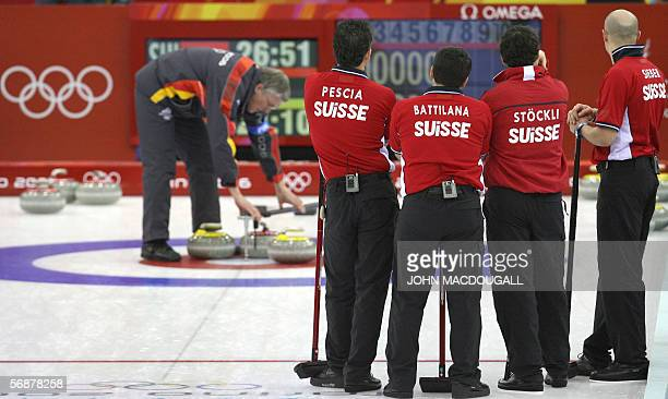 The Swiss curling team stands by as an official measures distancesbetween stones during the Britain vs Switzerland match in the men's round robin...