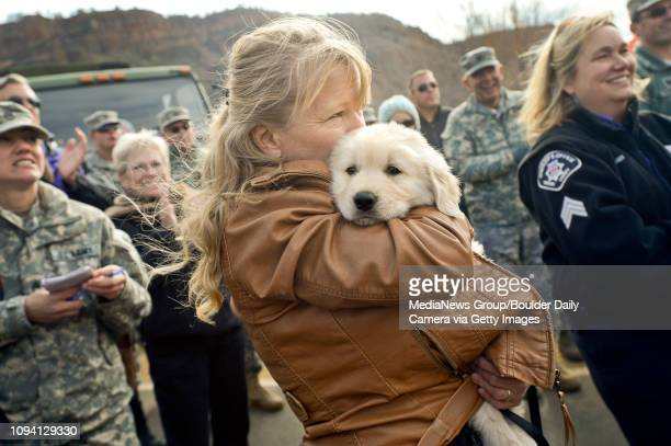 Pinewood Springs resident Geri Plank holds a dog named Chinook during a ceremony to reopen US 36 to Estes Park Monday Nov 4 near Lyons