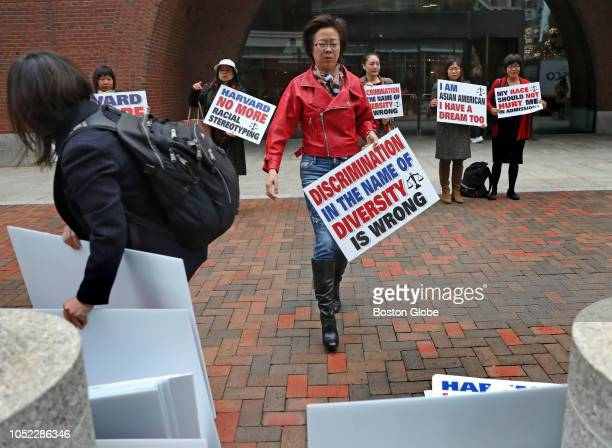 Ping Zhang holds a sign while demonstrating outside the John Joseph Moakley United States Courthouse on the opening day of Harvard University's...