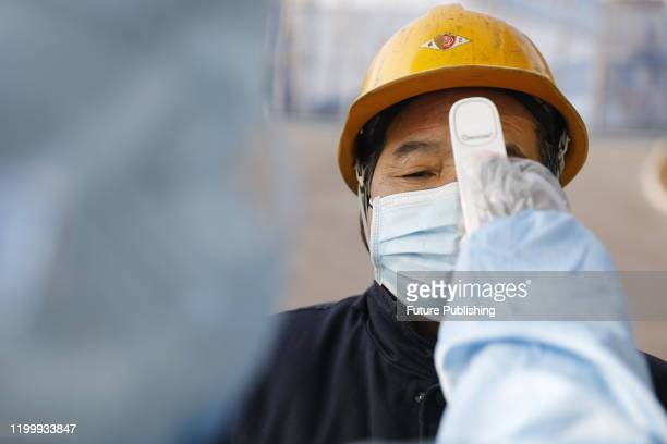 Pingdingshan, China - february 8, 2020 - Staff take temperature of workers entering the factory, Pingdingshan City, Henan Province, China, February...