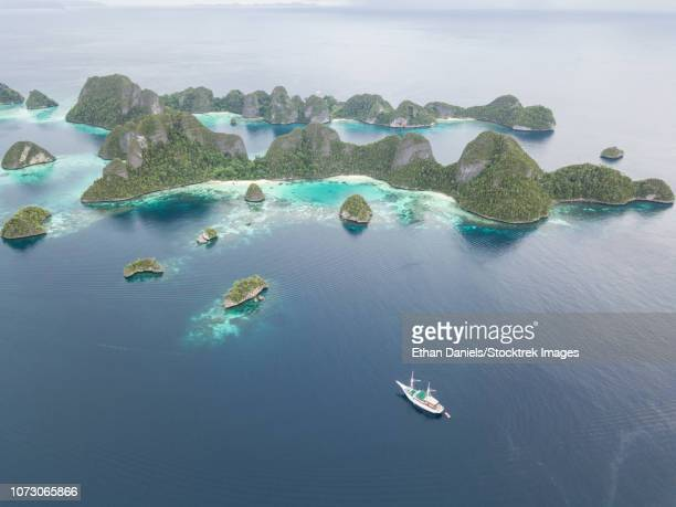 A Pinisi schooner sits at anchor in a remote area of Raja Ampat in eastern Indonesia.
