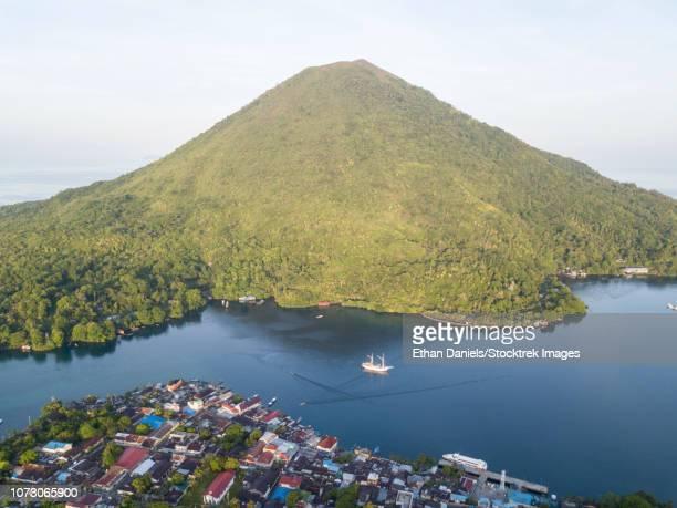 A Pinisi schooner sits at anchor next to Banda Api, a live volcano in the Banda Sea, Indonesia.