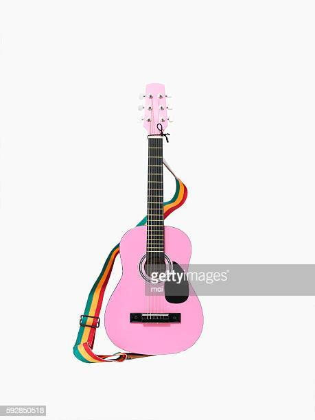 a pink acoustic guitar with a rainbow colored strap - strap stock pictures, royalty-free photos & images