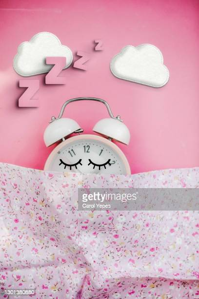pink alarm clock  sleeping in bed - pillow stock pictures, royalty-free photos & images