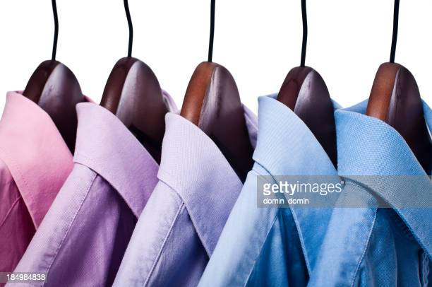 Pink and blue button down shirts on hangers