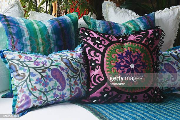 Pink and blue decorative pillows on bed