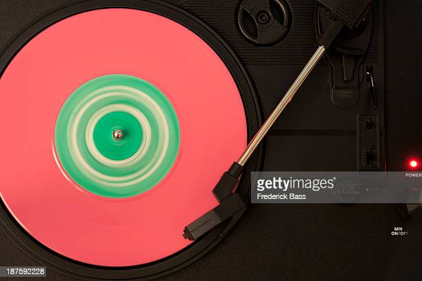 A pink and green vinyl record playing on a turntable