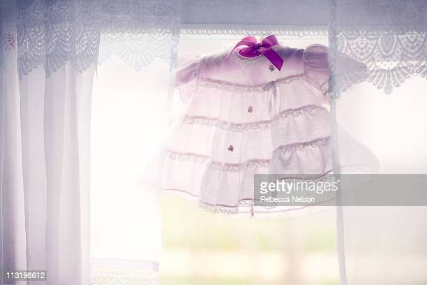 pink baby dress hanging in window - lace textile stock pictures, royalty-free photos & images