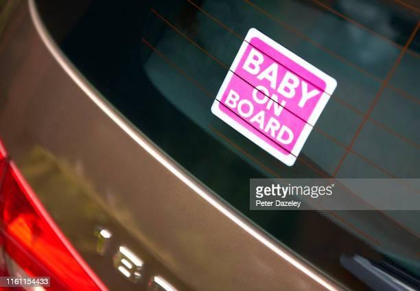 Pink Baby on Board sticker in rear view window of car