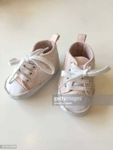 pink baby shoes - baby booties stock photos and pictures