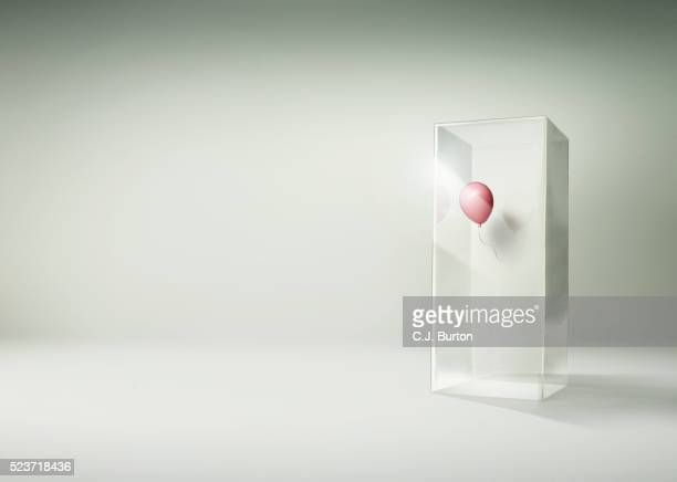 Pink balloon floating in side of a tall glass box