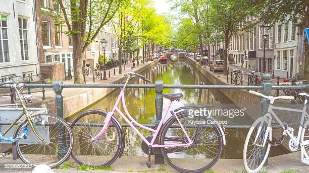 Pink Bicycle parked on bridge over a canal, Amsterdam
