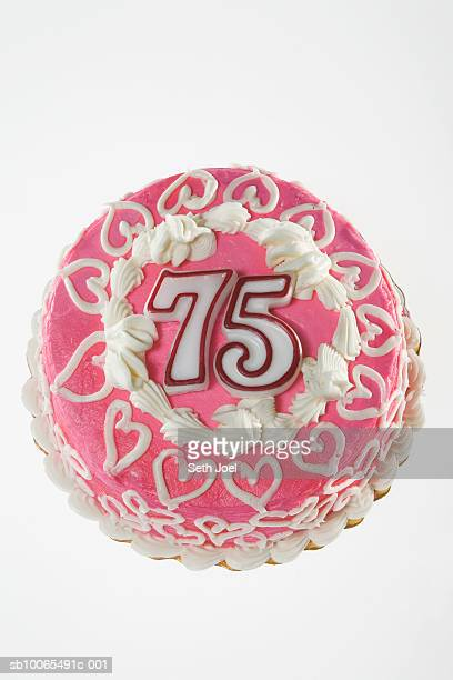 Pink birthday cake with whipped cream decoration and number 75, white background