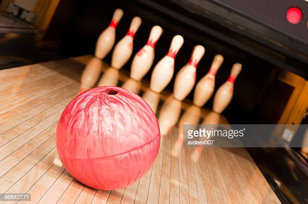 A pink bowling ball going toward pins