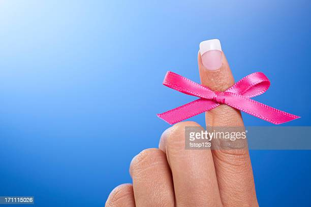 Pink breast cancer awareness reminder ribbon on index finger.