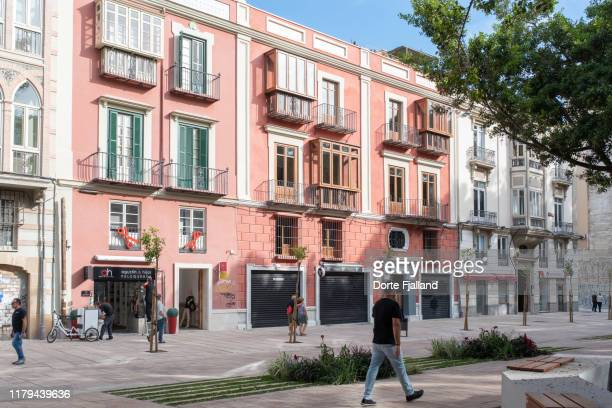 pink building on the renovated alameda in málaga, spain with some people walking in the front - dorte fjalland stock pictures, royalty-free photos & images
