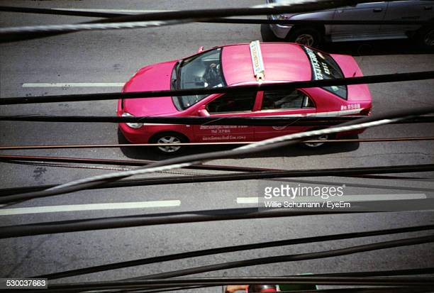 Pink Car On Street Seen Through Cables