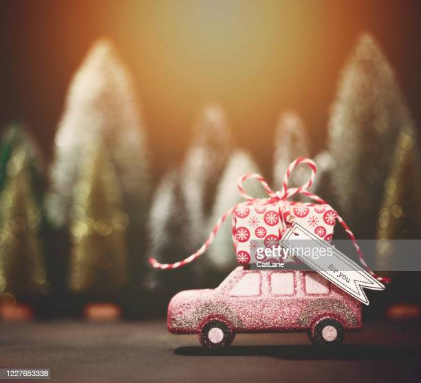 pink car transporting christmas gift. christmas holiday background. - car decoration stock pictures, royalty-free photos & images