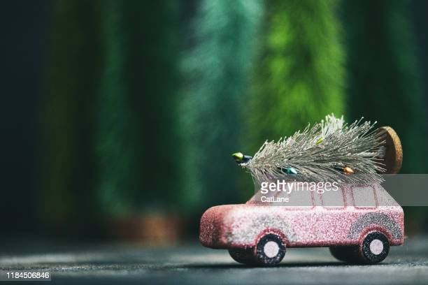 pink car transporting christmas tree. christmas holiday background. - car decoration stock pictures, royalty-free photos & images