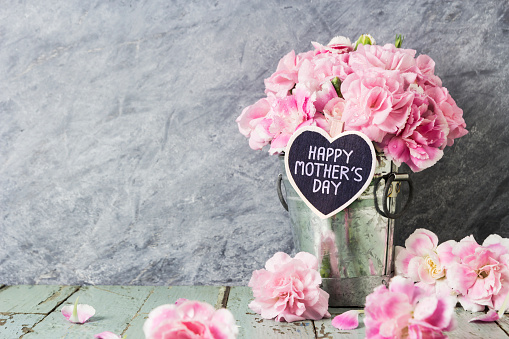 Pink carnation flowers in zinc bucket with happy mothers day letter on wood heart 649121536