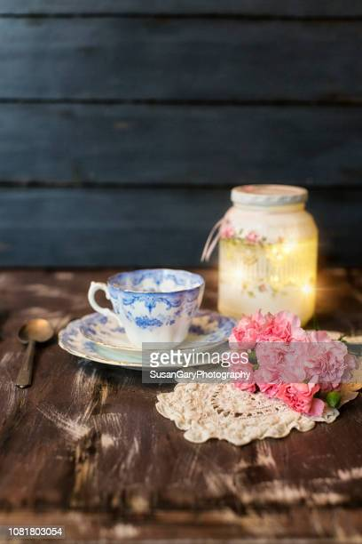 pink carnations with tea cup and lighted jar still life - doily stock photos and pictures