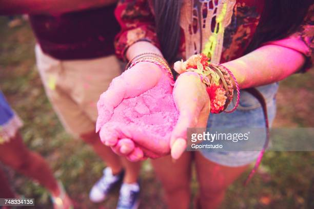 Pink chalk cupped in young womans hands at festival