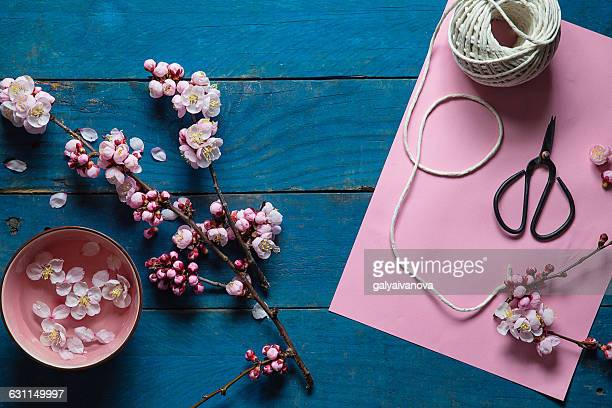 pink cherry blossom, scissors, paper and string
