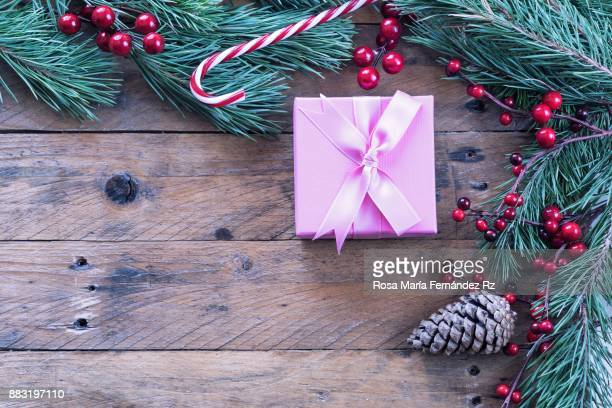 Pink Christmas gift box with bow, fir tree branches, mistletoe seed, candy cane and pine cone on old wooden background. Directly above and copy space