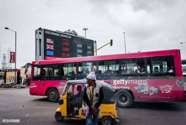 A pink city bus advertising Mcvities United Biscuits UK Ltd digestive biscuits drives past a giant advertising screen showing US dollar British pound...