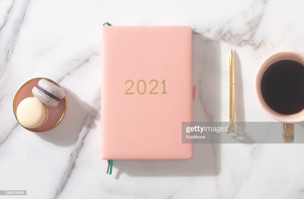 Pink coral colored diary for the year 2021, pen, coffee, macaron cookie. Marble background : Stock Photo