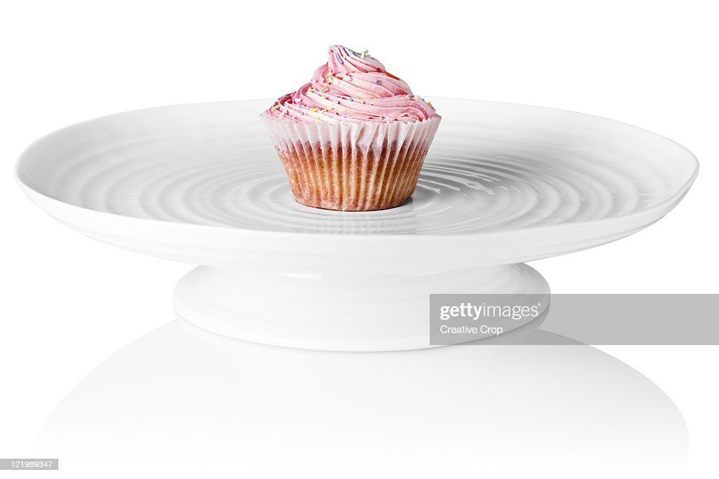 Pink cup cake sat on a porcelaine cake stand : Stock Photo