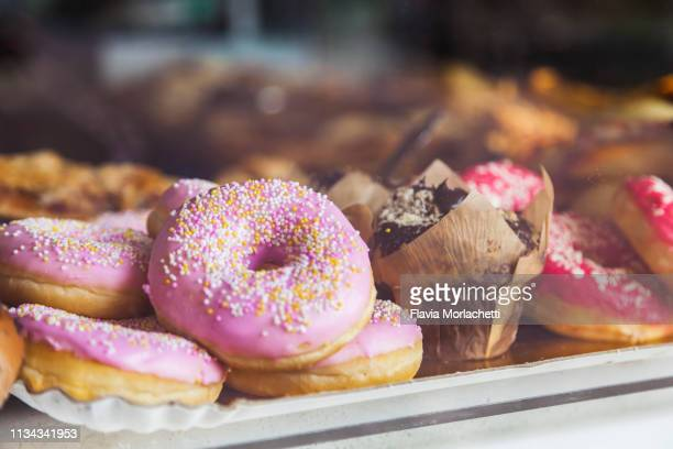 pink donuts in store window - donut stock pictures, royalty-free photos & images