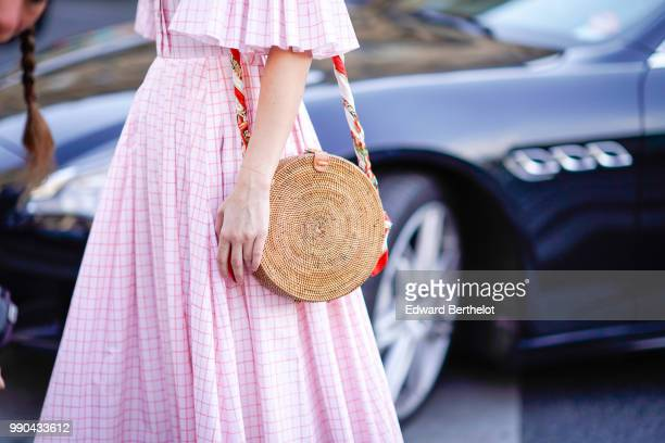 A pink dress and a circular straw bag outside Schiaparelli during Paris Fashion Week Haute Couture Fall Winter 2018/2019 on July 2 2018 in Paris...