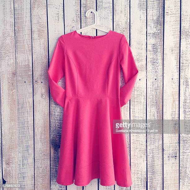 pink dress hanging from wooden wall - dress stock pictures, royalty-free photos & images