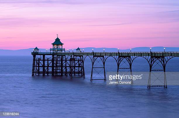 a pink dusk sky over clevedon pier in somerset. - clevedon pier stock pictures, royalty-free photos & images