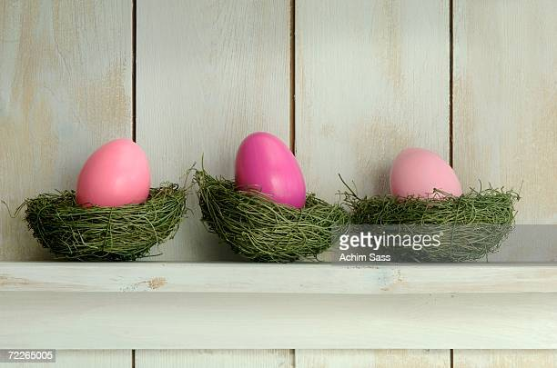 Pink easter eggs in nest on wooden shelf, close-up