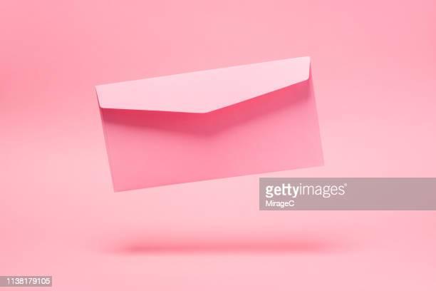 pink envelope mid-air - fourniture de bureau photos et images de collection