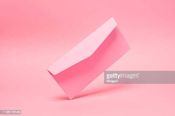pink envelope mid-air - pink background stock pictures, royalty-free photos & images