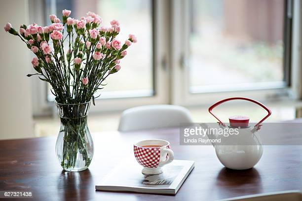 pink flower bouquet, teapot and cup of tea on a table